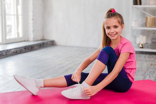 Ritratto di una ragazza sorridente che si siede sulla stuoia di esercitazione che lega il suo laccio Foto Gratuite
