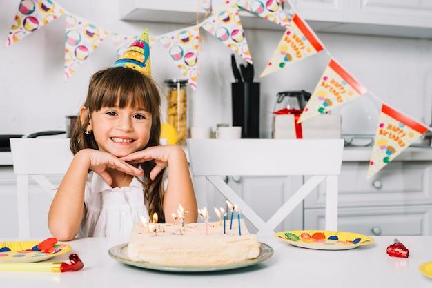 Ritratto di una ragazza sorridente di compleanno che si siede alla tabella con la torta di compleanno Foto Gratuite