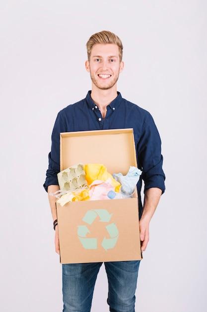 Ritratto di una scatola di cartone della tenuta dell'uomo in pieno di immondizia con l'icona di riciclaggio Foto Gratuite