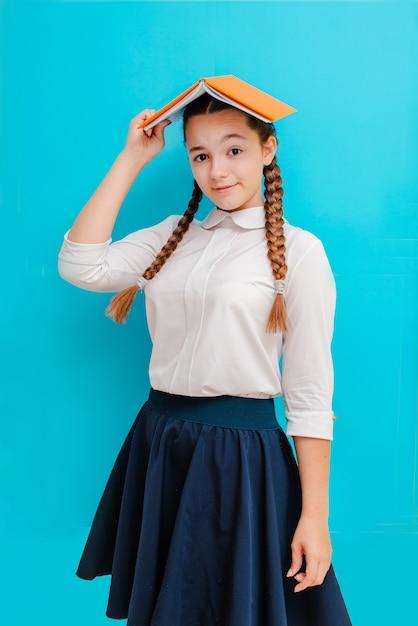 Ritratto di una scolara in vetri con i manuali dei libri sul blu giallo Foto Premium