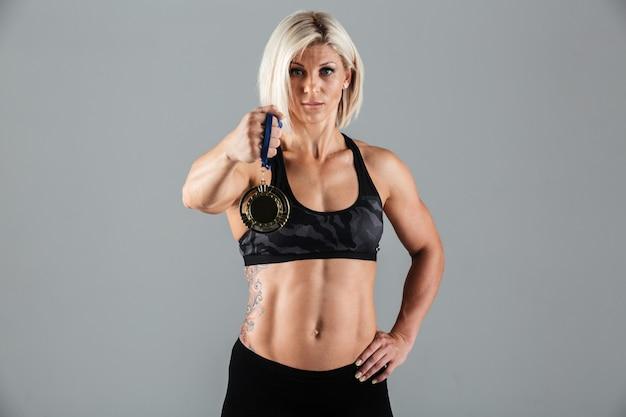 Ritratto di una sportiva atletica fiduciosa che mostra una medaglia Foto Gratuite
