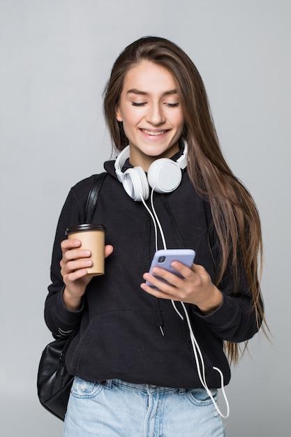 Ritratto di una studentessa attraente allegra con lo zaino che ascolta la musica con le cuffie mentre mostrando il telefono cellulare dello schermo in bianco e ballare isolato sopra la parete bianca Foto Gratuite