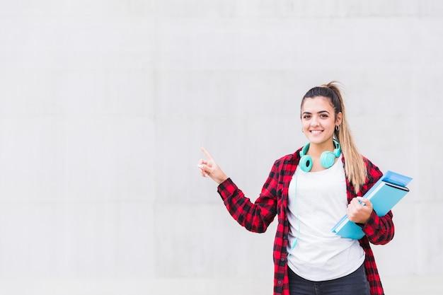 Ritratto di una studentessa in possesso di libri in mano che punta il dito in piedi contro il muro grigio Foto Gratuite