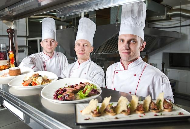 Ritratto di uno chef con cibi cotti in cucina nel ristorante. Foto Premium