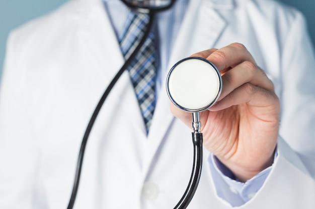 Ritratto di uno stetoscopio della holding del medico per esame obiettivo Foto Gratuite