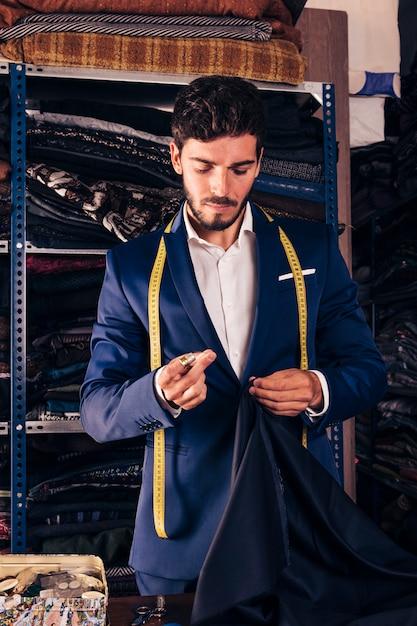 Ritratto di uno stilista maschio cucito tessuto con ago Foto Gratuite