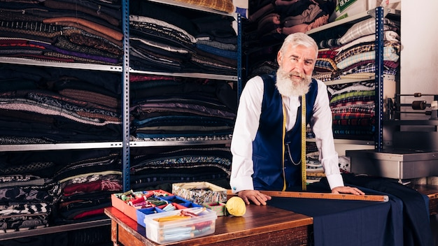 Ritratto di uno stilista maschio senior nel suo negozio che guarda l'obbiettivo Foto Gratuite
