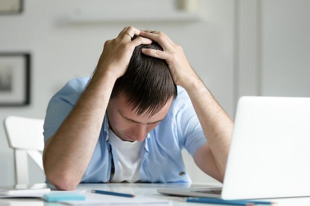 Ritratto di uomo afferrare la testa in disperazione vicino al computer portatile Foto Gratuite