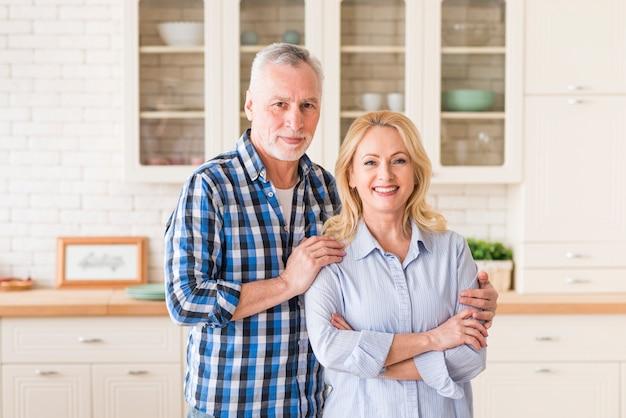 Ritratto di uomo anziano felice in piedi dietro la donna in cucina Foto Gratuite