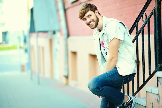 Ritratto di uomo bello in abiti eleganti hipster. ragazzo attraente in posa in strada Foto Gratuite
