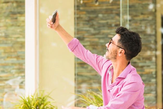 Ritratto di uomo bello in camicia rosa prendendo selfie sul cellulare Foto Gratuite