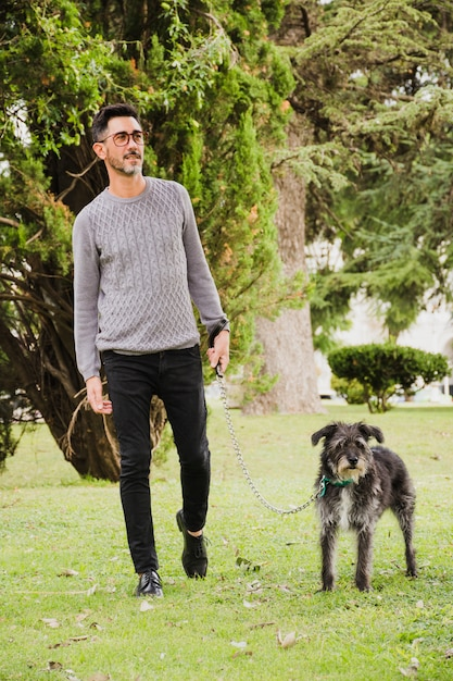 Ritratto di uomo che cammina con il suo cane sull'erba verde nel parco Foto Gratuite