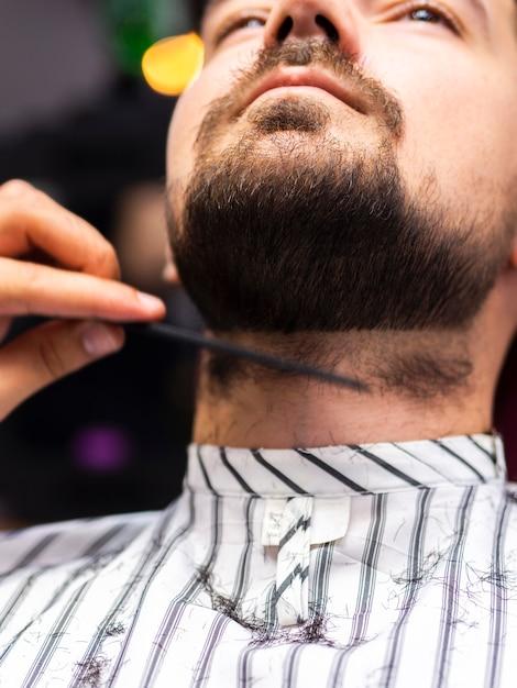 Ritratto di uomo che ottiene il taglio della barba Foto Gratuite
