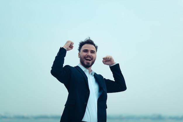 Ritratto di uomo d'affari di giovane elegante uomo sorridente in tuta in posa su un yacht Foto Premium