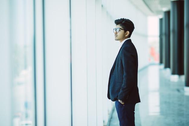 Ritratto di uomo d'affari indiano sorridente in ufficio moderno Foto Gratuite