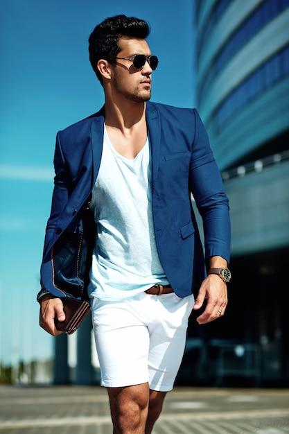 Ritratto di uomo di modello maschio sexy moda bello vestito in abito elegante in posa sulla strada. cielo blu Foto Gratuite
