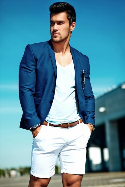 Ritratto di uomo di modello maschio sexy moda bello vestito in abito elegante in posa sullo sfondo strada. cielo blu Foto Gratuite