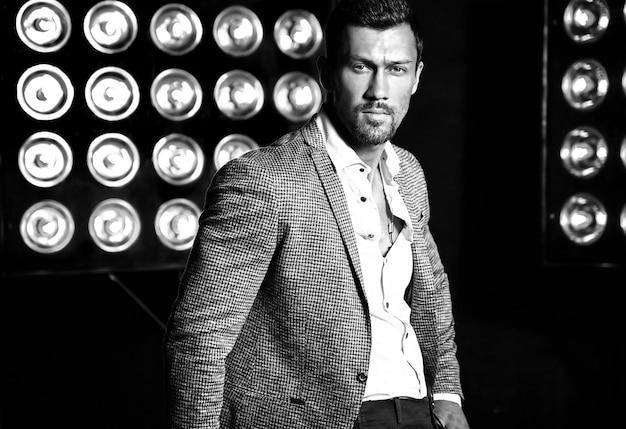 Ritratto di uomo di modello maschio sexy moda bello vestito in abito elegante su sfondo di luci di studio Foto Gratuite