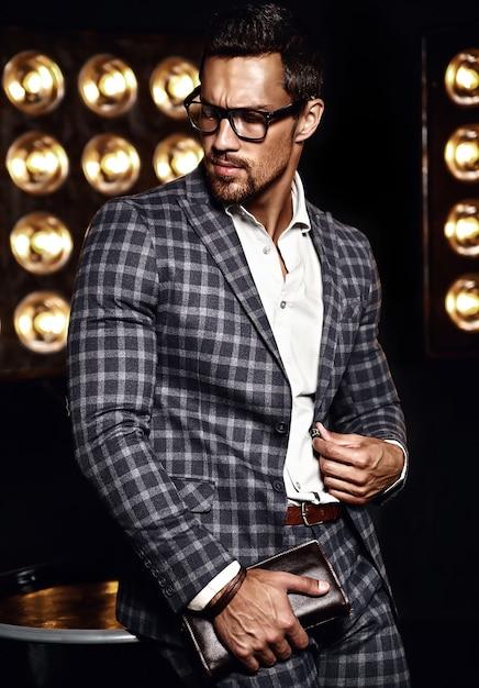Ritratto di uomo di modello maschio sexy moda bello vestito in abito elegante su sfondo nero luci studio in bicchieri Foto Gratuite