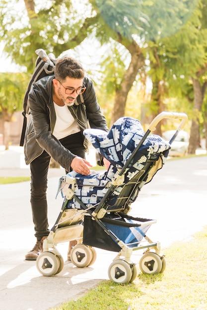 Ritratto di uomo elegante che trasportano il suo bambino dal passeggino nel parco Foto Gratuite
