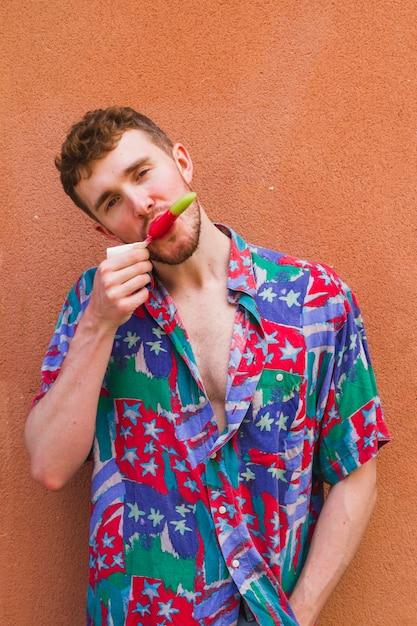 Ritratto di uomo elegante mangiare gelato Foto Gratuite