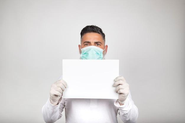 Ritratto di uomo in maschera chirurgica con un cartello bianco su sfondo bianco. Foto Premium