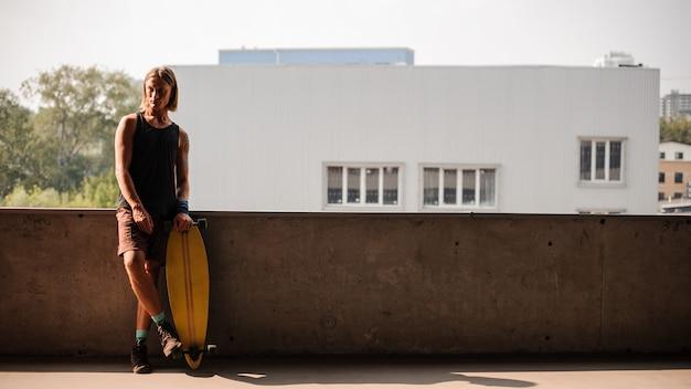 Ritratto di uomo in piedi con un longboard Foto Premium