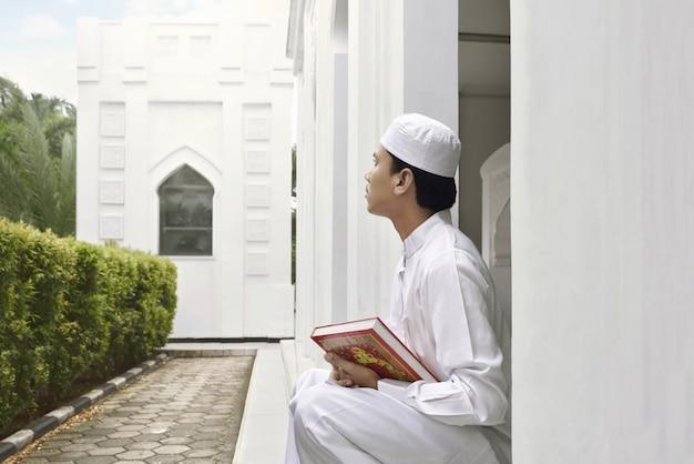 Ritratto di uomo musulmano asiatico che tiene corano Foto Premium