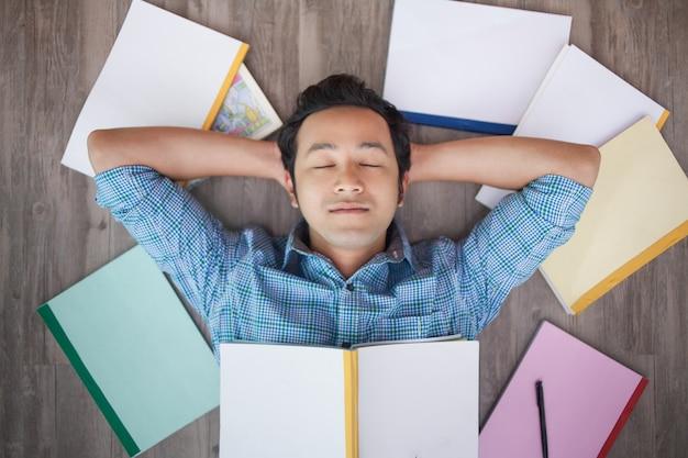 Ritratto di uomo napping asiatico sul pavimento tra i libri Foto Gratuite