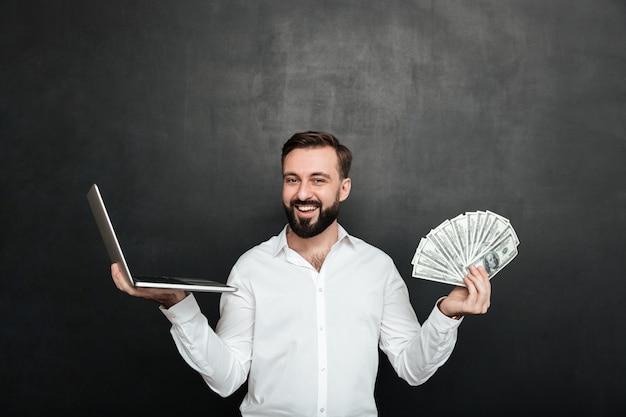 Ritratto di uomo ricco allegro in camicia bianca che vince un sacco di valuta del dollaro dei soldi usando il suo taccuino sopra grigio scuro Foto Gratuite
