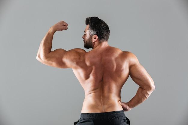 Ritratto di vista posteriore di un culturista maschio senza camicia muscolare Foto Gratuite