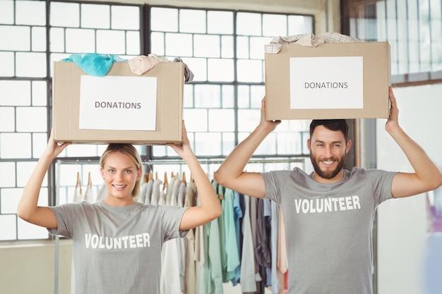 Ritratto di volontari che trasportano scatole di donazione sulla testa Foto Premium
