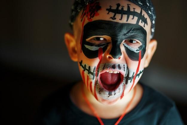 Ritratto emotivo di un ragazzo urlando con uno zombi spaventoso sul viso Foto Premium