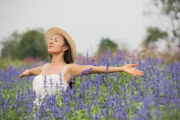 Ritratto esterno di una bella donna di mezza età dell'asia. ragazza attraente in un campo con i fiori Foto Gratuite
