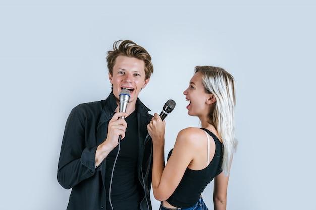 Ritratto felice del microfono della tenuta delle coppie e canta una canzone Foto Gratuite