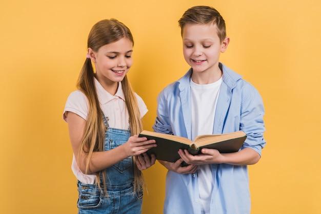Ritratto felice del ragazzo e della ragazza che leggono il libro che si leva in piedi contro la priorità bassa gialla Foto Gratuite