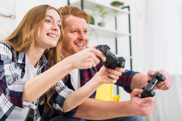 Ritratto felice di giovani coppie che giocano la console di gioco con le leve del joystick Foto Gratuite