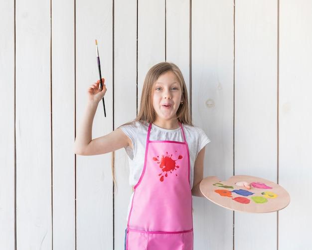 Ritratto felice di un pennello della tenuta della ragazza e di una tavolozza di legno in mani che stanno contro la parete di legno bianca Foto Gratuite