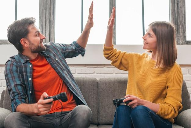 Ritratto felice di una giovane coppia che si siede sul divano dando il cinque a vicenda mentre si gioca video gioco Foto Gratuite