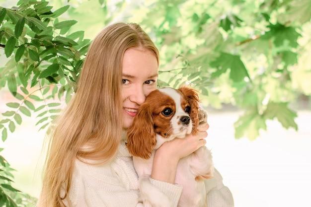 Ritratto felice ragazza bionda con i capelli lunghi che tiene carino cucciolo di razza cavalier king charles spaniel. Foto Premium