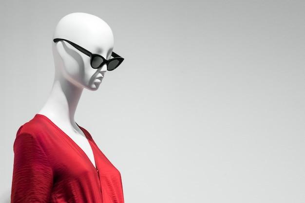 Ritratto femminile del manichino in occhiali da sole e vestito rosso. tema di vendita e pubblicità. copyspace per il testo Foto Premium