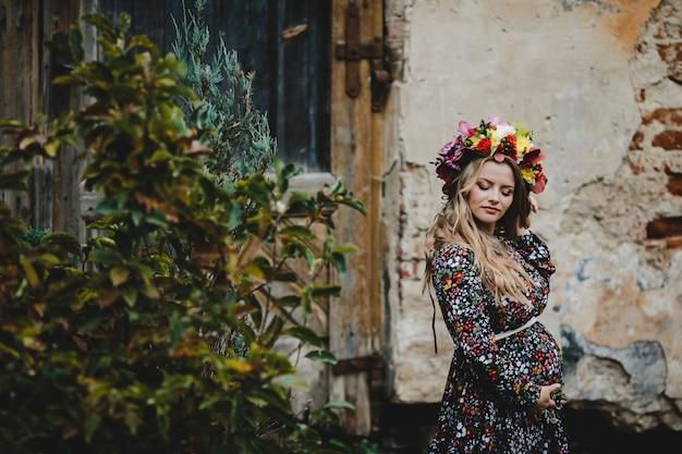 Ritratto femminile la donna incinta adorabile in corona di fiori pone Foto Gratuite