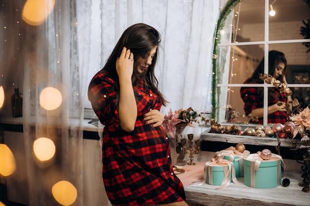 Ritratto femminile la donna incinta in camicia controllata posa nella stanza accogliente con l'albero di natale Foto Gratuite