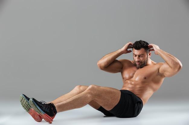 Ritratto integrale di un culturista maschio senza camicia di misura muscolare Foto Gratuite