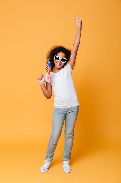 Ritratto integrale di una bambina africana allegra con la bandiera americana Foto Gratuite