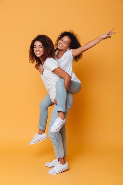 Ritratto integrale di una ragazza africana emozionante che trasporta sorellina Foto Gratuite