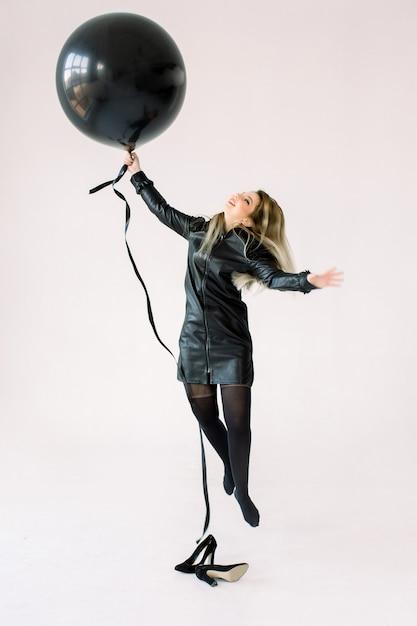 Ritratto integrale di una ragazza allegra in vestito nero che tiene grande mongolfiera mentre saltando e volando, esaminando macchina fotografica isolata sopra fondo bianco Foto Premium
