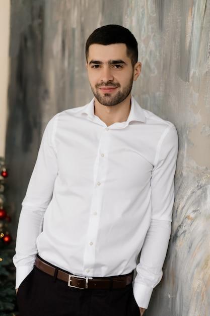 fb9f53468b Ritratto maschile l'uomo castana bello in camicia bianca e jeans ...