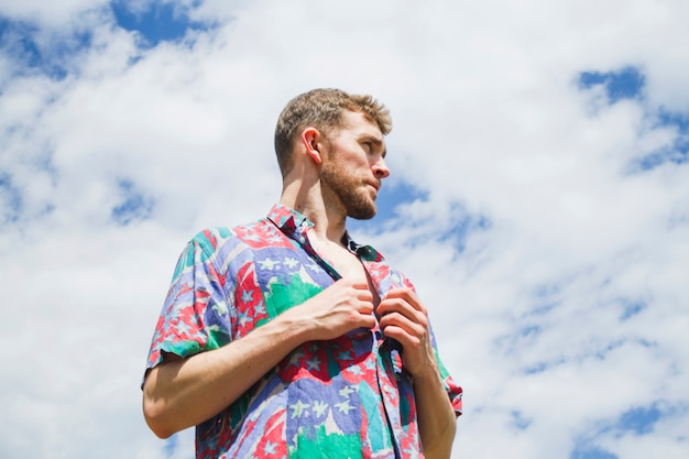 Ritratto medio basso del colpo dell'uomo alla moda che osserva via Foto Gratuite