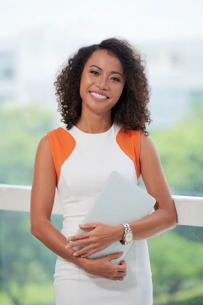 Ritratto medio della donna di affari che sta con il computer portatile alla finestra dell'ufficio Foto Gratuite